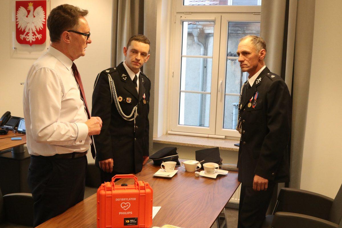 Burmistrz Śremu Adam Lewandowski przekazuje dh Wojciechowi Zagórskiemu Prezesowi i dh Przemysławowi Mielcarekowi Naczelnikowi OSP Pysząca defibrylator.
